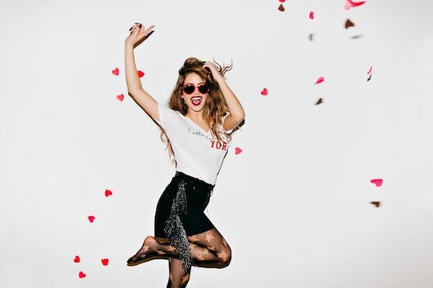 Emotionele vrouwelijke model in panty met plezier in de studio Gratis Foto