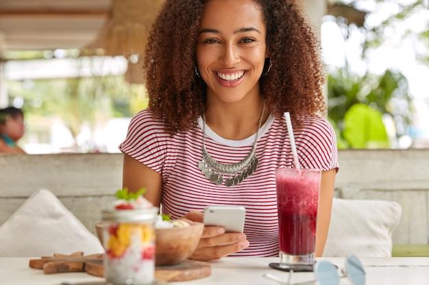 Emotionele zwarte jonge vrouw met fris haar, brede glimlach, moderne cellulaire bezit, maakt gebruik van gratis wifi in cafetaria voor netwerken, drinkt vers fruit smoothie, draagt casual t-shirt, heeft vrije tijd Gratis Foto