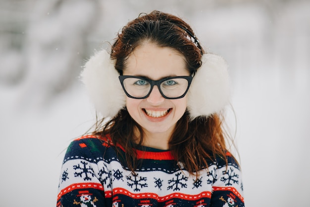En vrouw die kijkt glimlacht. de winterportret van jong mooi meisje die oormoffen, sweater het stellen in sneeuwpark dragen. Premium Foto