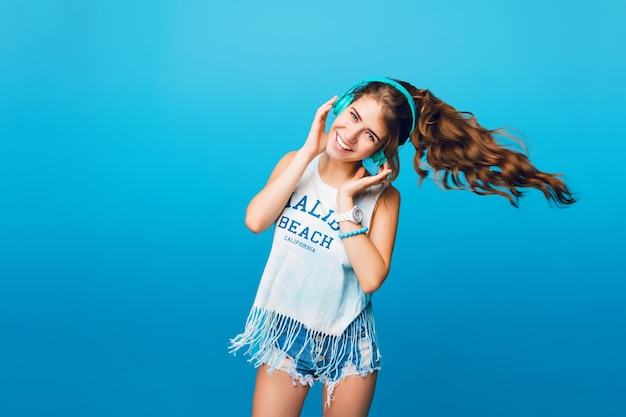 Energie meisje met blauwe koptelefoon luisteren naar muziek op blauwe achtergrond in de studio. ze draagt een wit t-shirt, korte broek. lang krullend haar in de staart vliegt vanuit beweging naar de zijkant. Gratis Foto