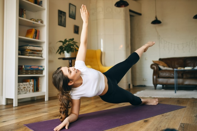 Energieke atletische jonge vrouw die binnenshuis traint, zijwaartse plankhouding doet die helpt bij het opbouwen van kracht in de kern, armen en benen. Gratis Foto