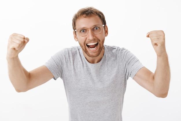 Energieke opgewonden en enthousiaste teamleider in bril en grijs t-shirt die vuisten opstak van gejuich, schreeuwend van het ondersteunen en aanmoedigen van werknemers die geamuseerd over een witte muur staan Gratis Foto