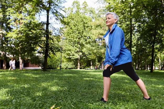 Energieke vrouwelijke gepensioneerde m / v in stijlvolle sportkleding kiezen voor een gezonde actieve levensstijl training op groen gras in het bos of park, lunges doen, gelukkig vreugdevolle blik hebben. ouderen, fitness en zomer Gratis Foto