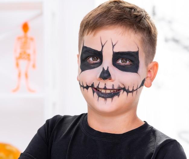 Enge jonge die jongen met gezicht voor halloween wordt geschilderd Gratis Foto