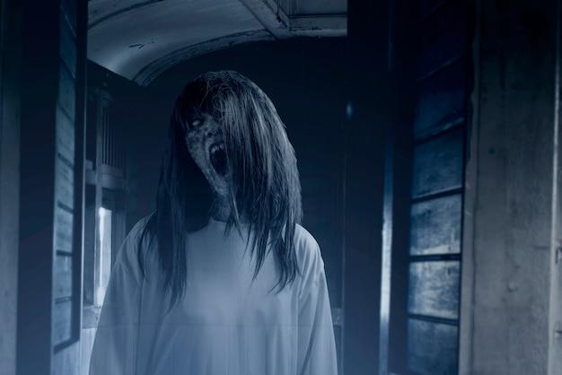 Enge spookvrouw met bloed en boos gezicht op de oude wagen Premium Foto