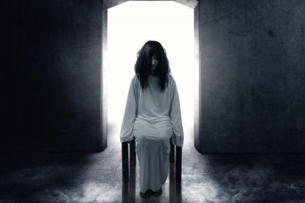 Enge spookvrouw met bloed en vuile gezichtszitting in de donkere ruimte Premium Foto