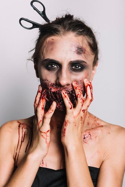 Enge vrouw met schaar in hoofd wat betreft gezicht Gratis Foto