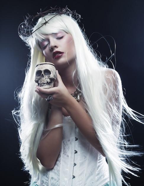 Engelachtige lange haarvrouw met schedel Premium Foto