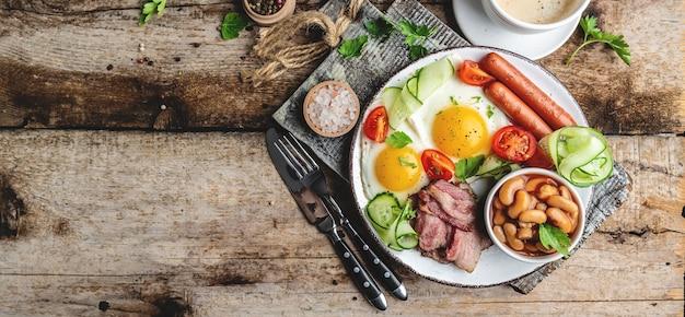 Engels ontbijt. gebakken ei, bonen, tomaten, spek en koffie. Premium Foto