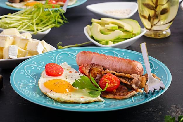 Engels ontbijt - gebakken ei, tomaten, worst en spek. Premium Foto