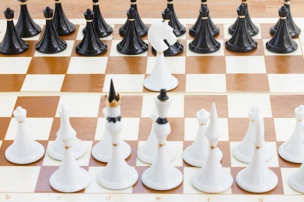 Enige witte ridder voor rij van zwart schaak Premium Foto