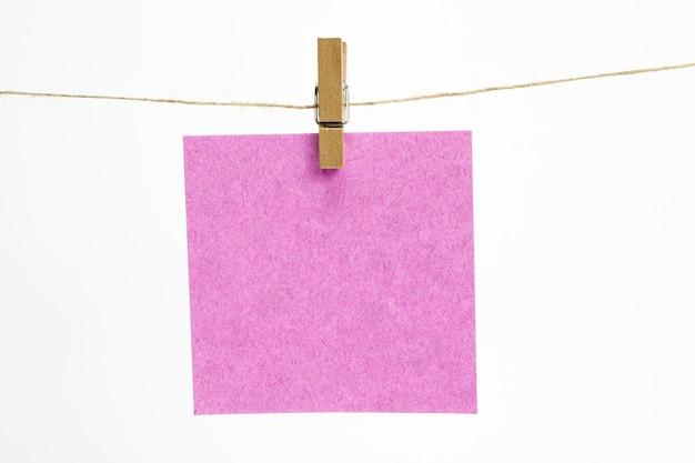 Enkele leeg vel papier voor notities die hangen aan een touw met wasknijpers en geïsoleerd op wit. Gratis Foto