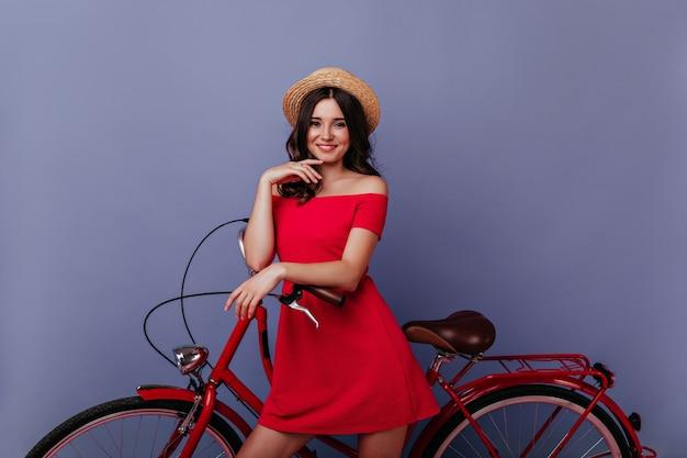 Enthousiast kaukasisch meisje dat zich dichtbij fiets met tevreden glimlach bevindt. binnenfoto van prachtige bruinharige vrouw die geniet van fotoshoot op paarse muur. Gratis Foto