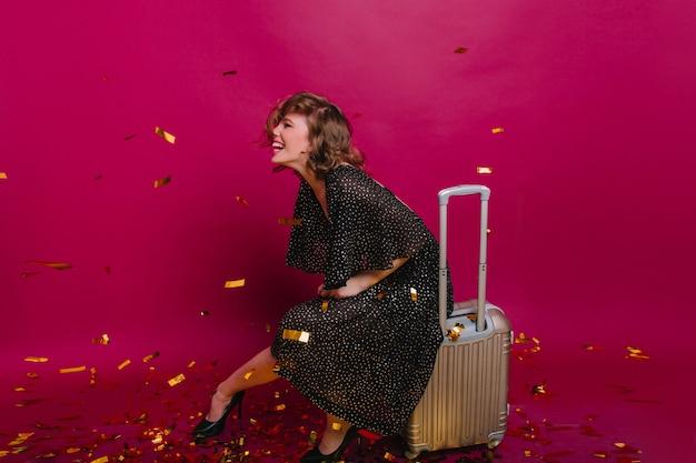 Enthousiast korthaar meisje in trendy jurk met plezier op feestje voor aanstaande reizen Gratis Foto