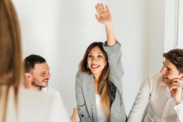 Enthousiaste jonge vrouw met opgeheven hand Gratis Foto