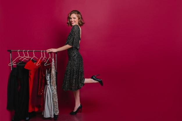 Enthousiaste vrouw in lange jurk poseren op één been in garderobe Gratis Foto
