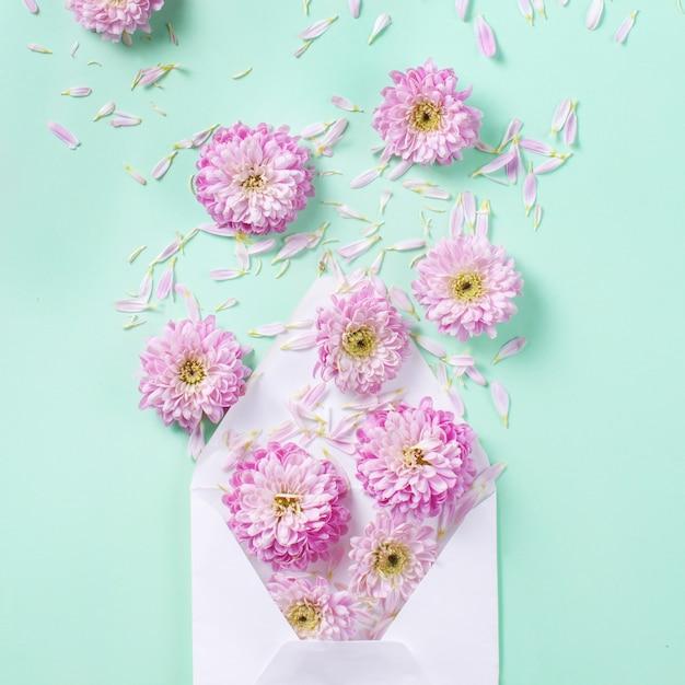 Envelop met bloemen en bloemblaadjes op een pastelroze Premium Foto