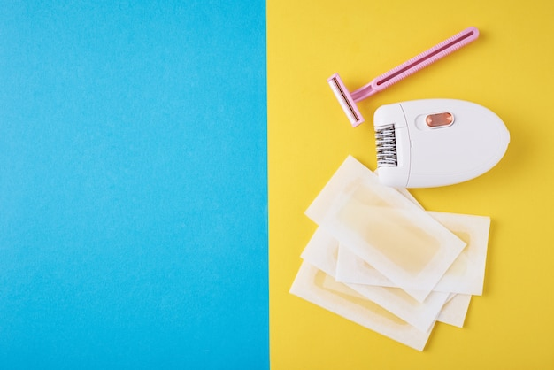 Epilator, scheermes en wax strips op blauw en geel Premium Foto