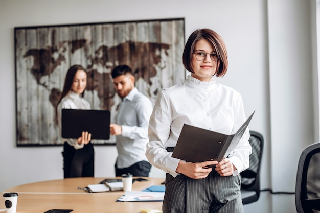 Ernstig, aantrekkelijk meisje in glazen werkt op kantoor. werksfeer concept Premium Foto