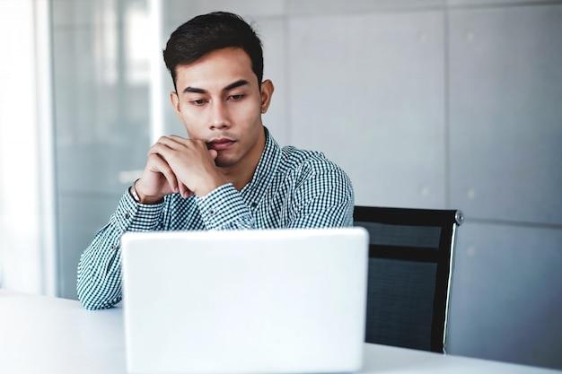 Ernstig jonge zakenman die aan computerlaptop werkt in bureau. hand op shin, zittend op een bureau met doordachte houding. geconcentreerde en slimme mannen Premium Foto
