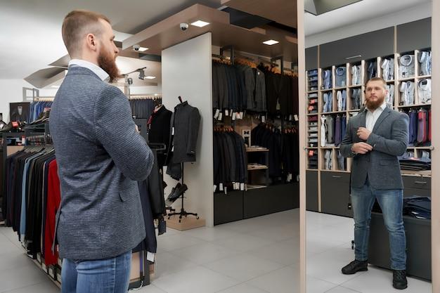 Ernstig mannetje dat spiegel bekijkt en slim kostuum kiest Premium Foto