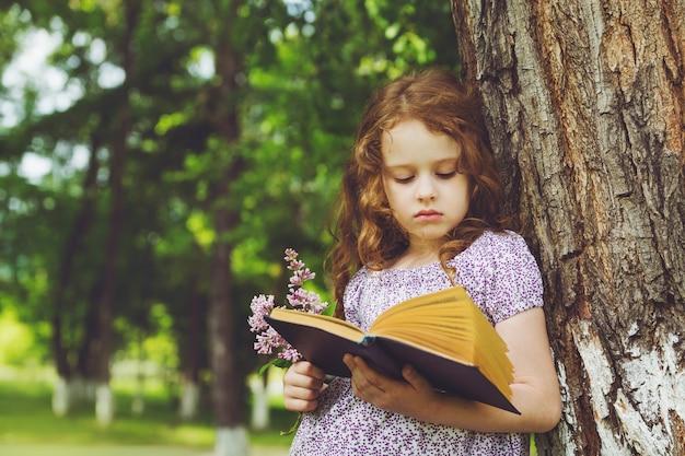 Ernstig meisje met een boek en een boeket van seringen in haar hand, die zich dichtbij grote boom bevinden. Premium Foto