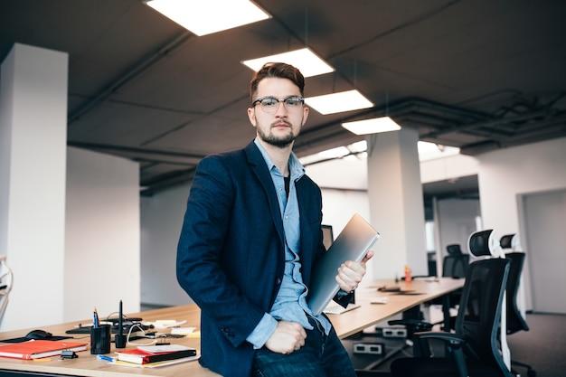 Ernstige aantrekkelijke man in glaasje staat in de buurt van de werkplek op kantoor. hij draagt een blauw shirt, een donkere jas, een laptop in de hand. hij kijkt naar de camera. Gratis Foto