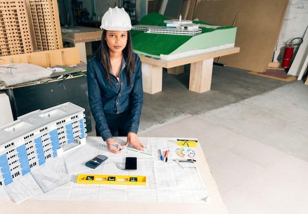 Ernstige afrikaans-amerikaanse dame in veiligheidshelm die zich dichtbij model van het voortbouwen op lijst bevinden Gratis Foto