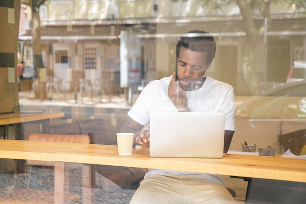 Ernstige afro-amerikaanse man typen op laptop en spreken op mobiel in co-werkruimte Gratis Foto