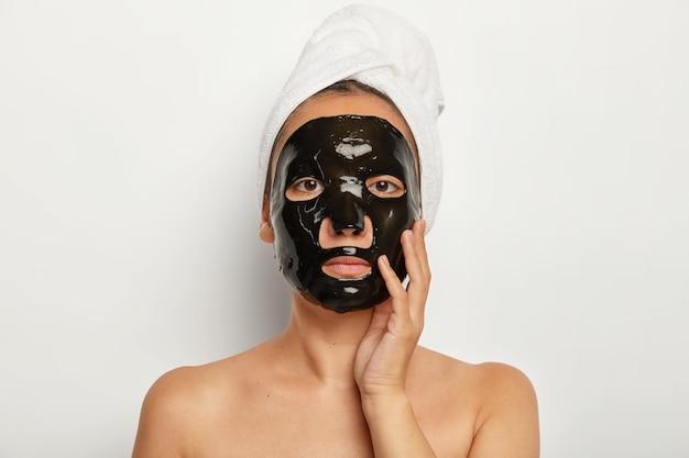 Ernstige aziatische vrouw heeft thuis cosmetische ingrepen, past een zwart zuiverend gezichtsmasker toe, ziet er recht uit, raakt zachtjes de wang aan, draagt een witte zachte handdoek op het hoofd Gratis Foto