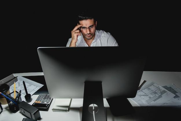 Ernstige aziatische zakenman die laat bij nacht in het bureau werkt Premium Foto