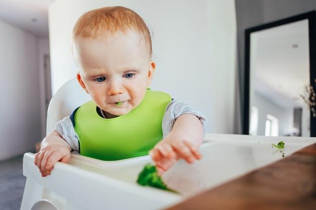 Ernstige babymeisje, zittend op een stoel en grijpen fingerfood Gratis Foto