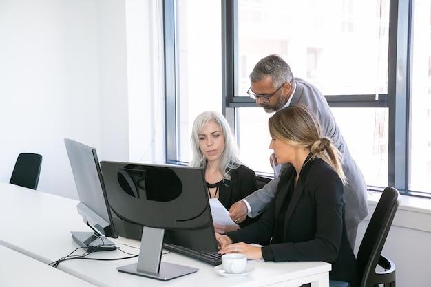 Ernstige bedrijfsgroep van drie analyseren van rapporten, zittend op de werkplek met monitoren samen, papieren vasthouden, herzien en bespreken. kopieer ruimte. zakelijke bijeenkomst concept Gratis Foto
