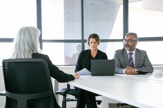 Ernstige bedrijfsmanagers die tijdens een sollicitatiegesprek met de sollicitant praten. achteraanzicht, kopieer ruimte. werkgelegenheid en loopbaanconcept Gratis Foto
