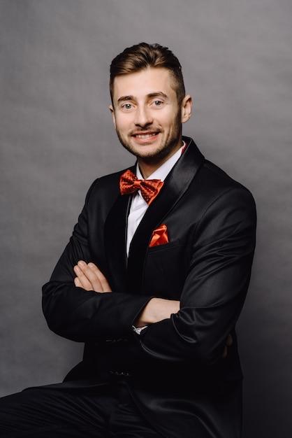Ernstige bedrijfsmens in elegante kostuumzitting met twee rijen knopen op een stoel op grijze studioachtergrond Premium Foto