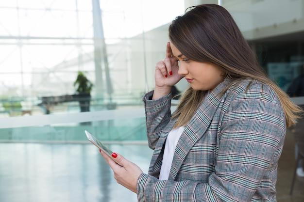 Ernstige bedrijfsvrouw die en tablet in openlucht denken gebruiken Gratis Foto