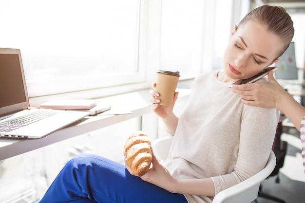 Ernstige busainessvrouw die op de telefoon spreekt en ontbijt eet Premium Foto