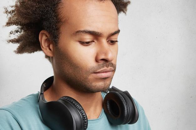 Ernstige donkere tiener met borstelig kapsel, luistert naar muziek met een koptelefoon Gratis Foto
