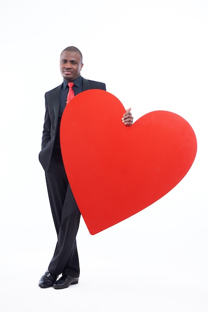 Ernstige en knappe afrikaanse man met groot rood hart Gratis Foto
