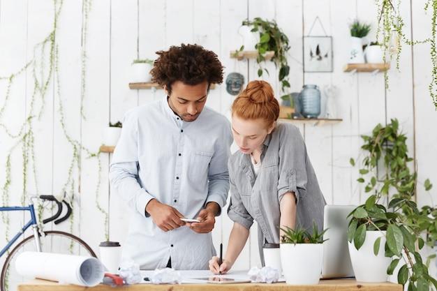Ernstige geconcentreerde man en vrouw staan in de buurt van een bureau omringd met moderne apparaten Gratis Foto
