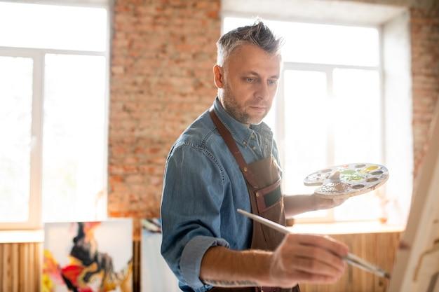 Ernstige geïnspireerde man met palet en penseel staande voor ezel en schilderen in werkplaats of atelier Premium Foto