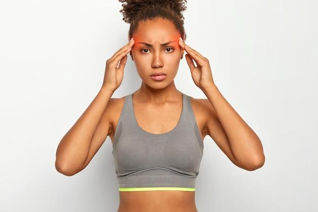 Ernstige gespannen afro-amerikaanse vrouw lijdt aan vreselijke pijn in tempels, heeft migraine, is uitgeput na lange fysieke training, draagt top, poseert tegen witte studiomuur Gratis Foto