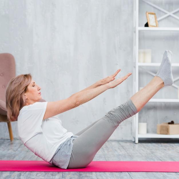 Ernstige hogere vrouw die haar benen op roze yogamat uitrekt Gratis Foto