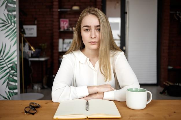 Ernstige jonge blanke vrouwelijke blogger zittend aan een bureau met notitieblok, glazen en mok geopend, notities maken tijdens het werken aan een nieuw artikel. mensen, levensstijl, baan, beroep en creativiteitconcept Gratis Foto