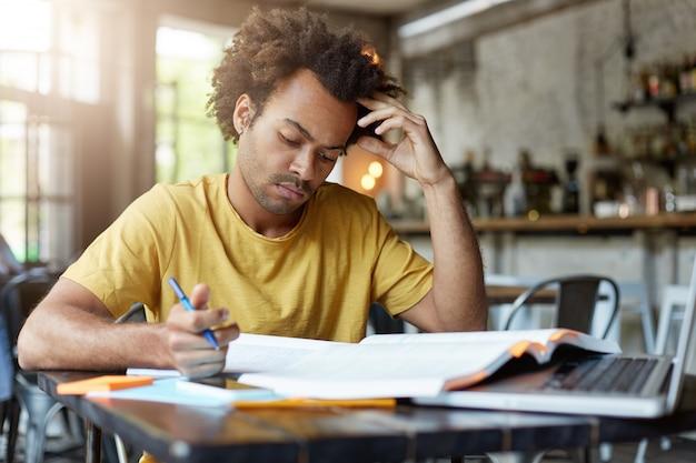 Ernstige jonge donkere man met donker haar en borstelharen draagt een geel t-shirt met geconcentreerde blik in zijn notitieboekje dat zich voorbereidt op zijn examen of lessen die in cafetaria zitten die hard werken Gratis Foto