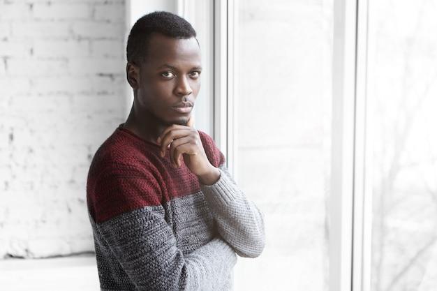 Ernstige jonge donkere ontwerper in gezellige warme trui met doordachte blik Gratis Foto
