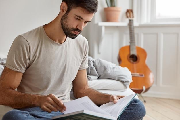 Ernstige jonge eigenaar van ondernemerschap, studeert bedrijfsliteratuur, gekleed in casual t-shirt, rust op bed in zijn kamer, akoestische gitaar staat in de muur. mensen, thuis, studeren, lezen concept Gratis Foto