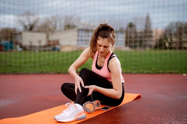 Ernstige jonge geschiktheidsmeisje die verwonde steel houden terwijl buiten het zitten op de oranje mat dichtbij het voetbalgebied. Premium Foto