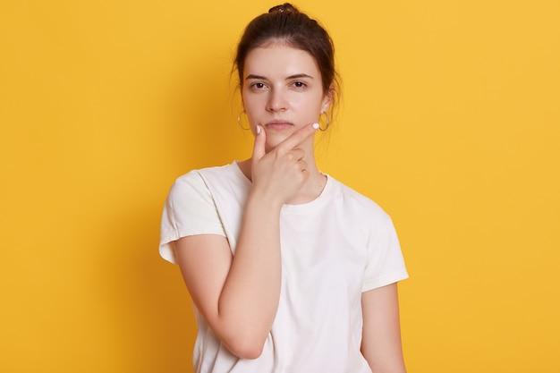 Ernstige jonge jonge vrouw die witte t-shirt draagt Gratis Foto