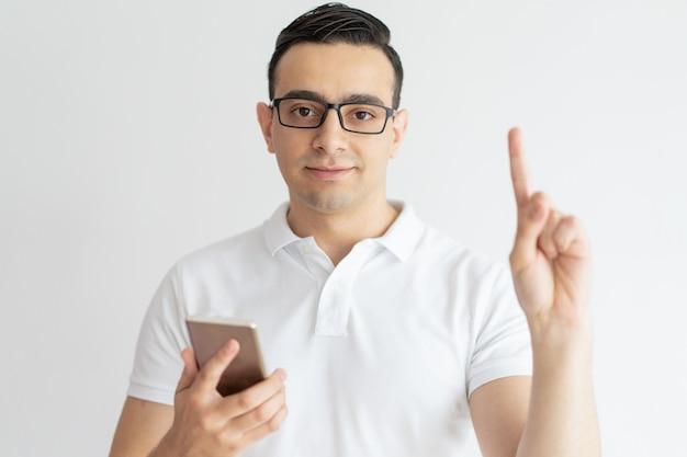 Ernstige jonge kerel die naar omhoog en smartphone houdt houdt Gratis Foto